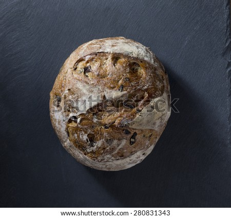 Round bread loaf on Black Slate Board. - stock photo