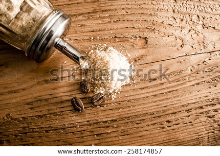 Round Cane granulated Sugar bowl lie on three coffee beans Old retro vintage aged wooden texture board table Empty space for inscription Coffee drink concept idea symbol Natural ingredients - stock photo