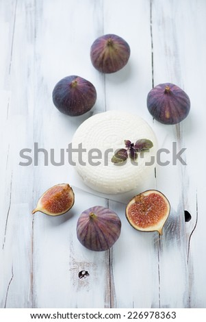 Round cheese and ripe fig fruits, vertical shot, high angle view - stock photo