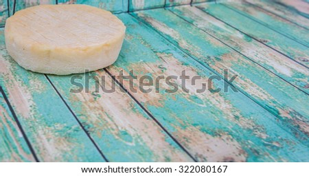 Round cheese over wooden background - stock photo