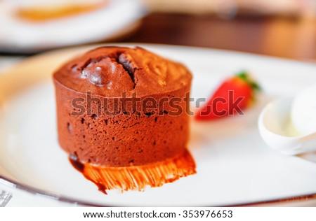 Round chocolate muffin (cake) on white plate - stock photo