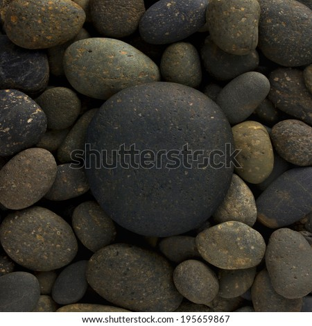 round circle shape of big sea stone laid on a pile of nature pebbles or a group of rocks. can use for background or texture  - stock photo