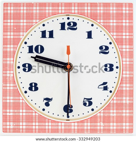 Round clock face on red striped background showing half past nine o'clock - stock photo