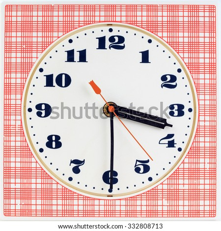 Round clock face on red striped background showing half past three o'clock - stock photo