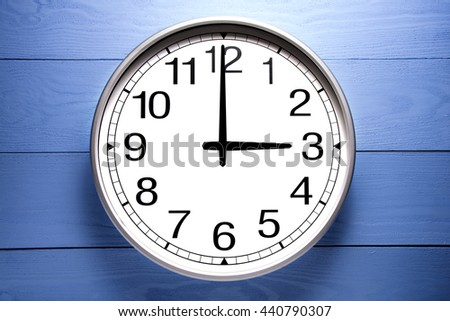 Round clock shows shows at 3 o'clock, clock on blue background - stock photo