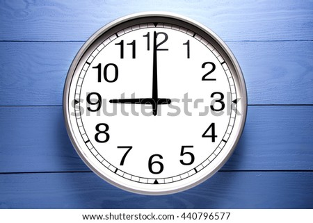 Round clock shows shows at 9 o'clock, clock on blue background - stock photo