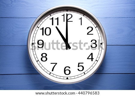 Round clock shows shows at 11 o'clock, clock on blue background - stock photo