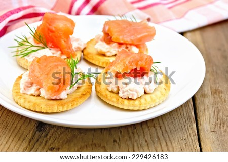 Round crackers with cream, dill and salmon in the plate, napkin on a wooden boards background - stock photo