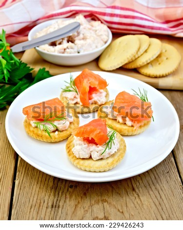 Round crackers with cream, dill and salmon in the plate, napkin, parsley on a wooden boards background - stock photo