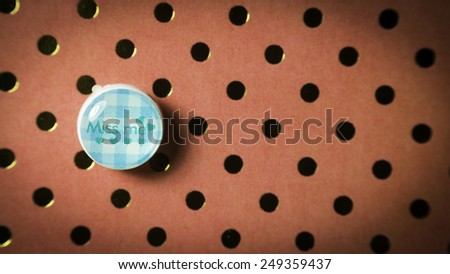 Round cute thumbtack or pushpin for whiteboard, notice board, gift card or special occasions with Miss Me message on polka dot vintage patterns background. Slightly defocused and close-up shot - stock photo
