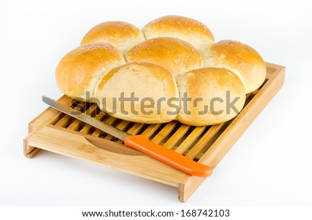 Round flower shaped bread and knife on cutting board - stock photo