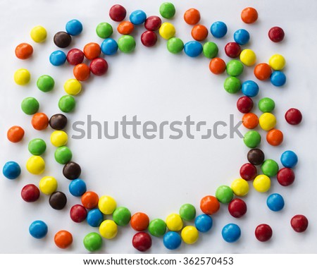 Round frame look like sun of colorful chocolate candies on a white background with space for your text Valentines Day concept - stock photo