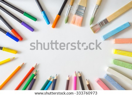 Round frame, made from painting brushes, felt-tip pens, chalks, colored pencils lying randomly on white background - stock photo
