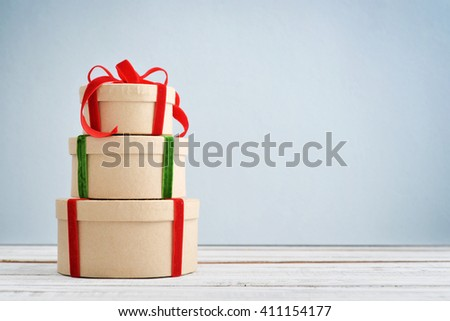 Round gift boxes with red and green ribbons on blue background - stock photo