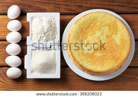 Round homemade golden biscuit cake on a plate, flour, sugar and eggs on wooden table. Ingredients for the cake. The cake and the ingredients from which it was prepared - stock photo