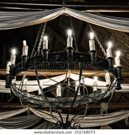 Round iron chandelier in an old tavern. - stock photo