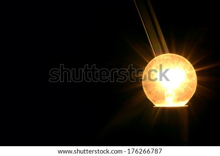 round light bulb shines in the darkness - stock photo