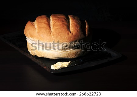 Round loaf of bread on a baking tray - stock photo