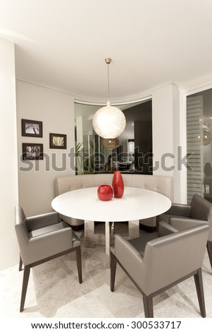 Round lunch table in a corner surrounded by cozy armchairs - stock photo