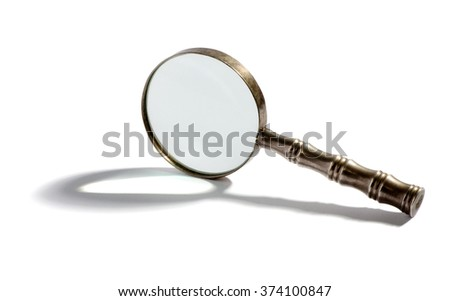 Round metal magnifying glass balanced on its side casting a shadow over a white background with copy space - stock photo