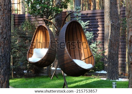 Round modern furniture plastic wicker chairs in garden  - stock photo