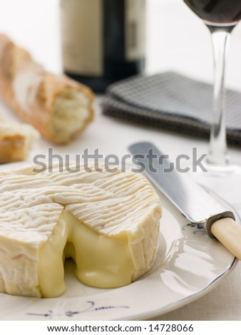 Round of camembert cheese with French stick and Red Wine - stock photo
