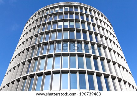 round office building on blue sky background - concrete and glass - stock photo