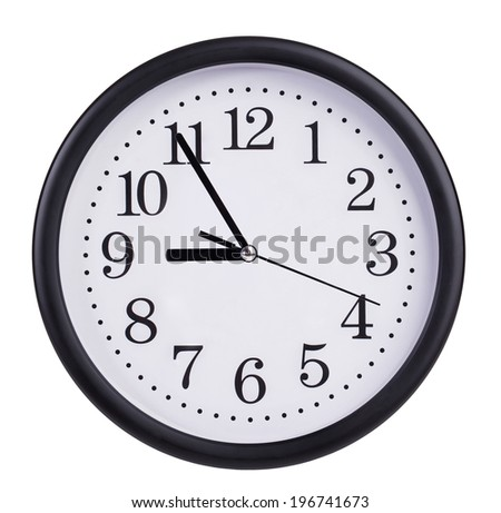Round office wall clock shows five to nine - stock photo