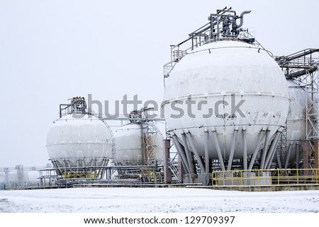 round oil tanks under snow cover - stock photo