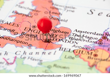 Round red thumb tack pinched through city of London on England map. Part of collection covering all major capitals of Europe. - stock photo