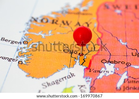 Round red thumb tack pinched through city of Oslo on Norway map. Part of collection covering all major capitals of Europe. - stock photo