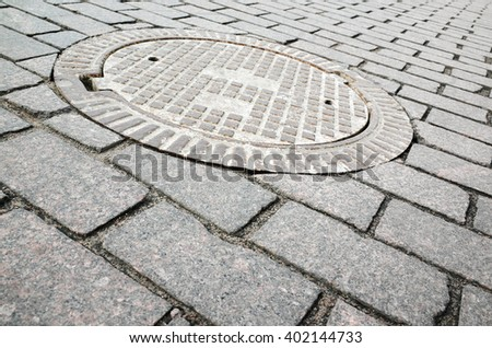 Round rusted hatch in urban cobblestone pavement, sewer manhole cover - stock photo