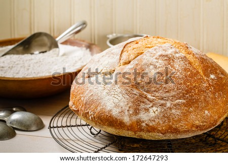 Round rustic artisan bread rests on a vintage wire cooling rack surrounded by a baking utensils and an old wood bowl full of flour - stock photo