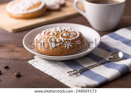Round shaped gingerbread cookies with cup of black coffee on wooden table - stock photo