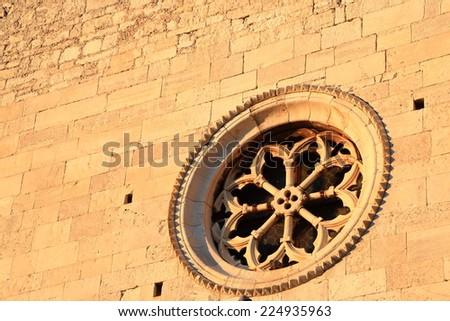 Round stone window of the facade of an old church in Venetian town near Adriatic sea, Pula, Croatia - stock photo