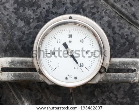 Round thermometer on gray metallic background - stock photo