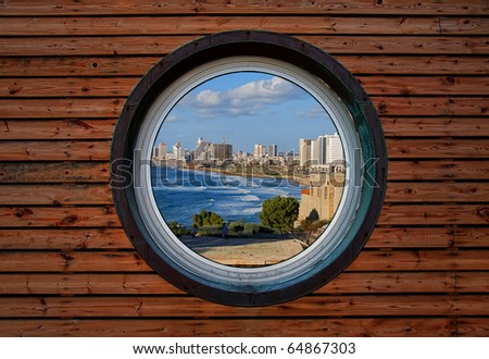 Round window of the wooden house with panoramic view on Tel-Aviv (Israel) - stock photo
