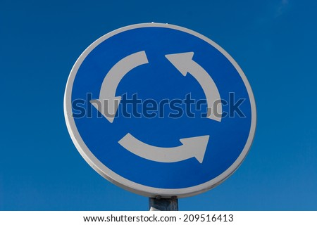 Roundabout road sign against blue sky - stock photo