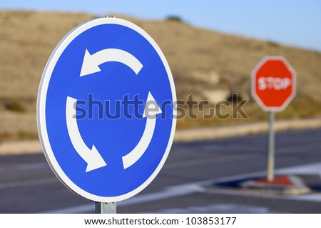 roundabout signal and halt sign in a road - stock photo