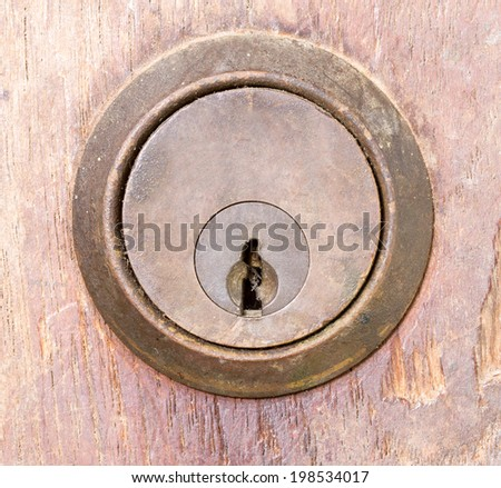 rounded aged keyhole on wooden wall - closed up - stock photo