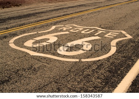 Route 66 pavement sign with Mojave desert  - stock photo