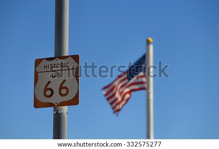 Route 66 Road Sign on the historic US highway with an american flag blowing in the background - stock photo