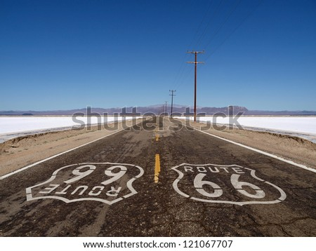 Route 66 sign painted on rough Mojave desert salt flat highway pavement. - stock photo