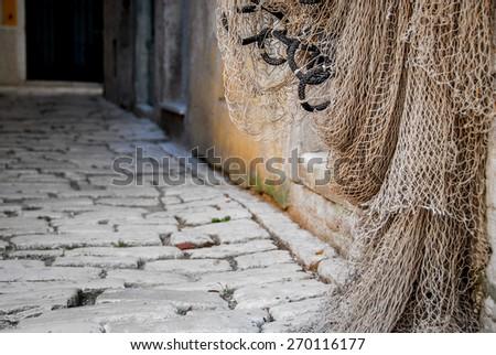 Rovinj old town, Croatia. Fishing nets hanging on the door. - stock photo