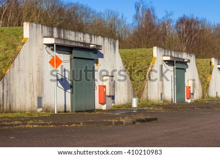 Row Ammunition bunker camouflaged with grass on a military complex - stock photo