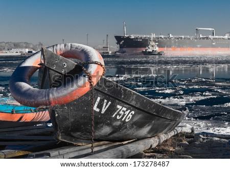 Row boat at freezing bank of river - stock photo