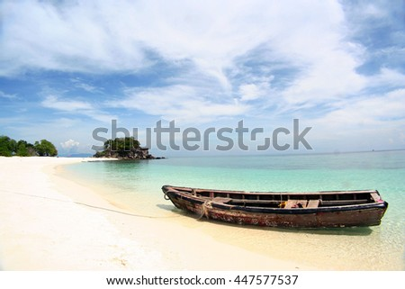 Row boat moor on the beach with blue sky and white sand - stock photo