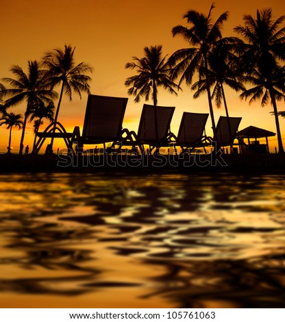 Row deckchairs with water reflection on beach at sunset, Tanjung Aru, Malaysia. - stock photo