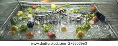 Row food showcase in a restaurant or shop with fish fruit and vegetable - red paprika lemon green salad tomatoes apple and one bottle vine Seafood lie inside fridge in ice  - stock photo