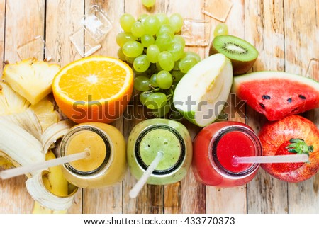 Row Fresh Juices Smoothie Three Bottles Red Green Yellow Color Fruits Water Melon Strawberry Apple Kiwi Grapes Orange Mango Pomegranate Tropical Selective focus Wooden Table - stock photo